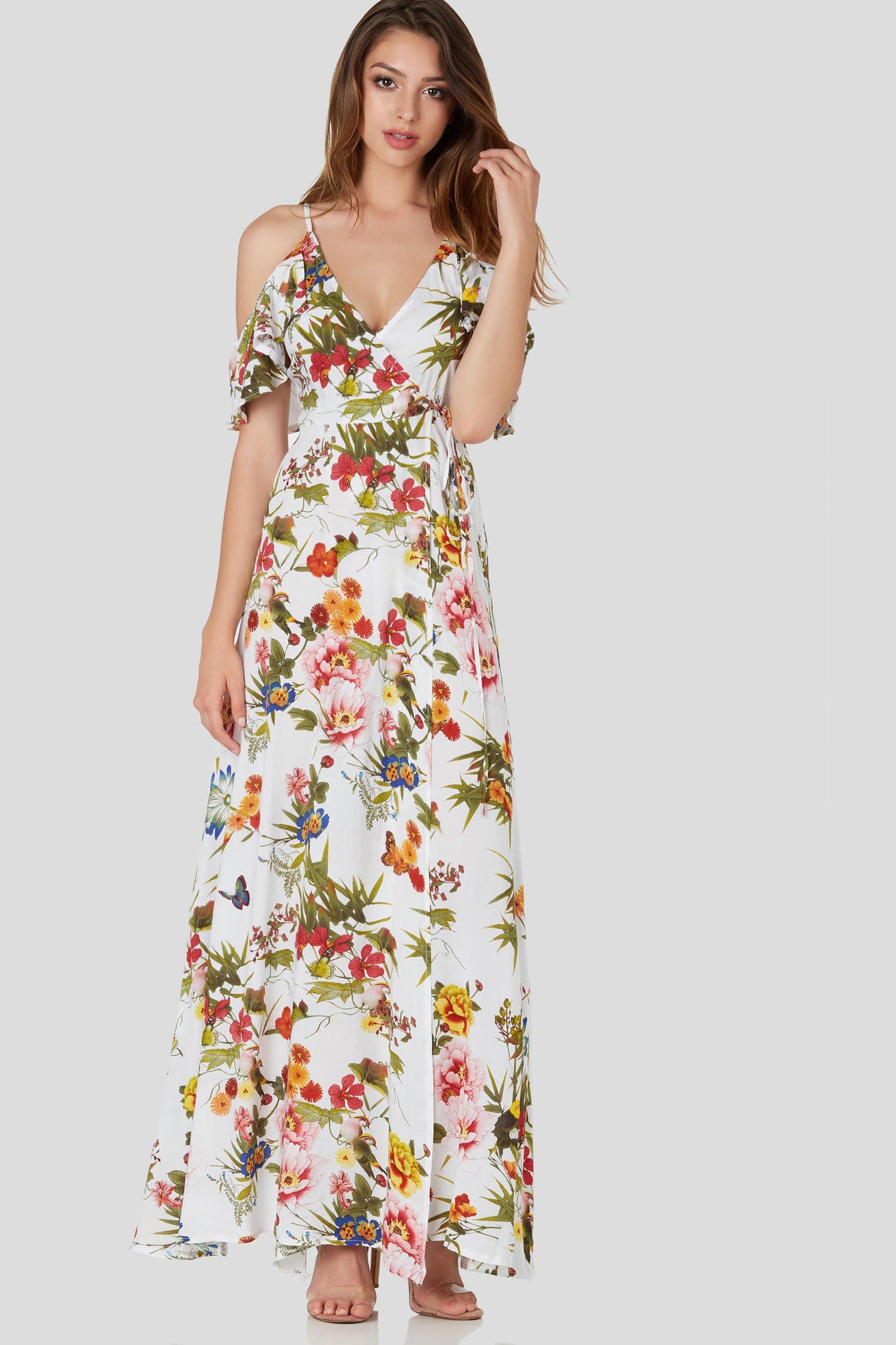 Flowy cold shoulder maxi dress with colorful floral patterns throughout. Flirty ruffle sleeves with wrap front closure.