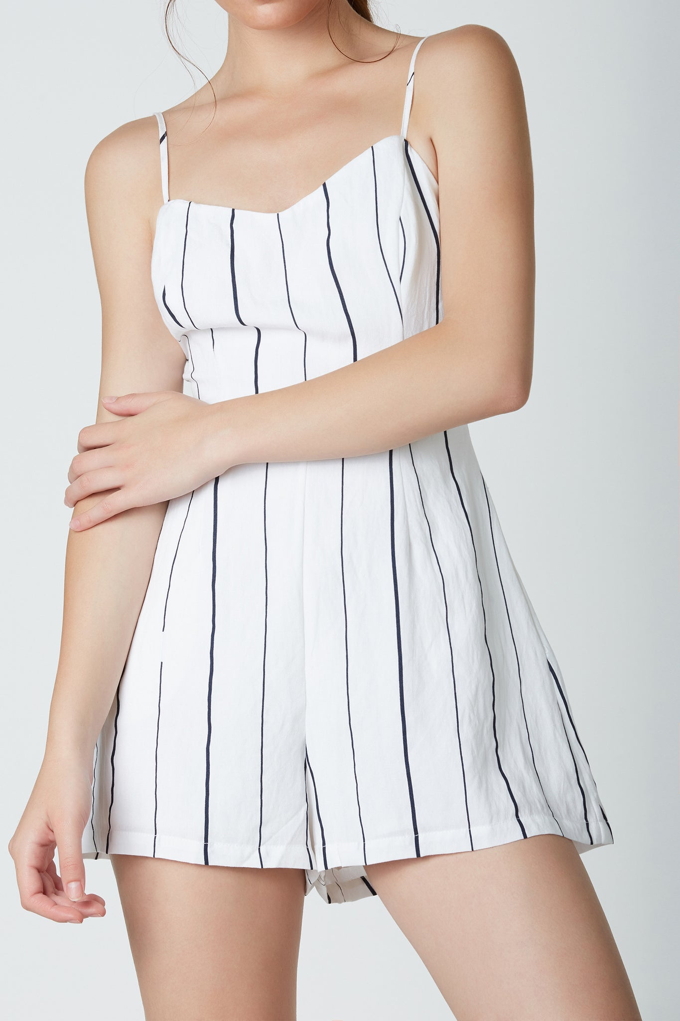 Chic sleeveless romper with stripe patterns throughout. Adjustable shoulder straps with cut out in back and ties for added detail.
