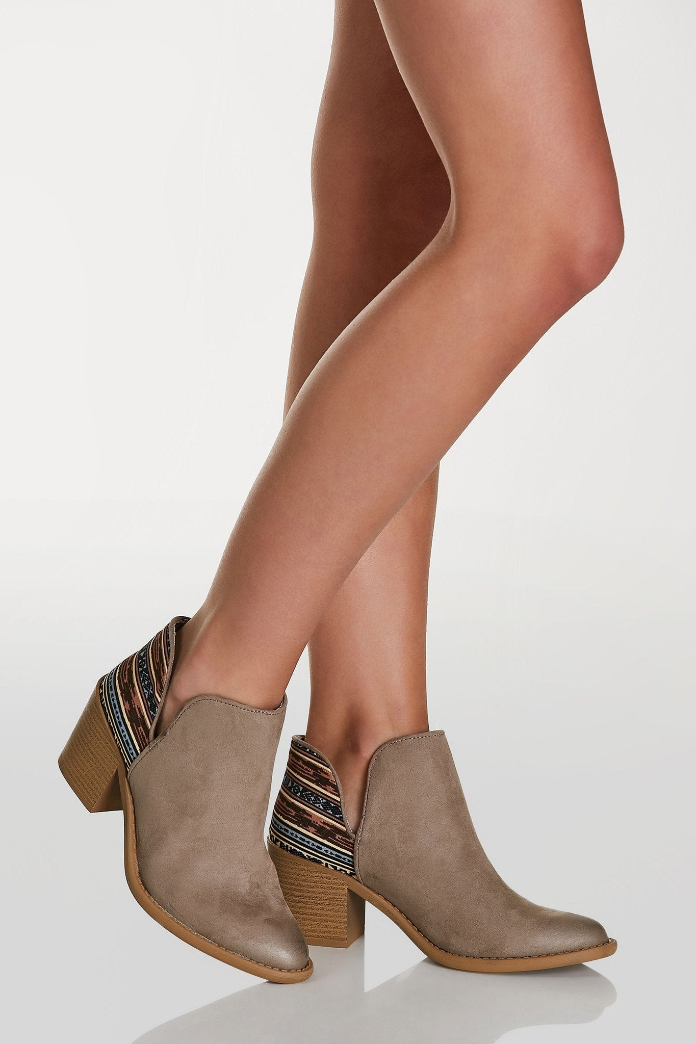 Faux suede ankle booties with side cut outs and tribal print contrast. Block heels and pointed toe tinish.