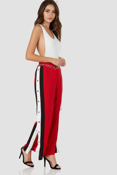 Trendy high rise pants with button zip closure. Contrast stripe detailing with snap buttons down each side.