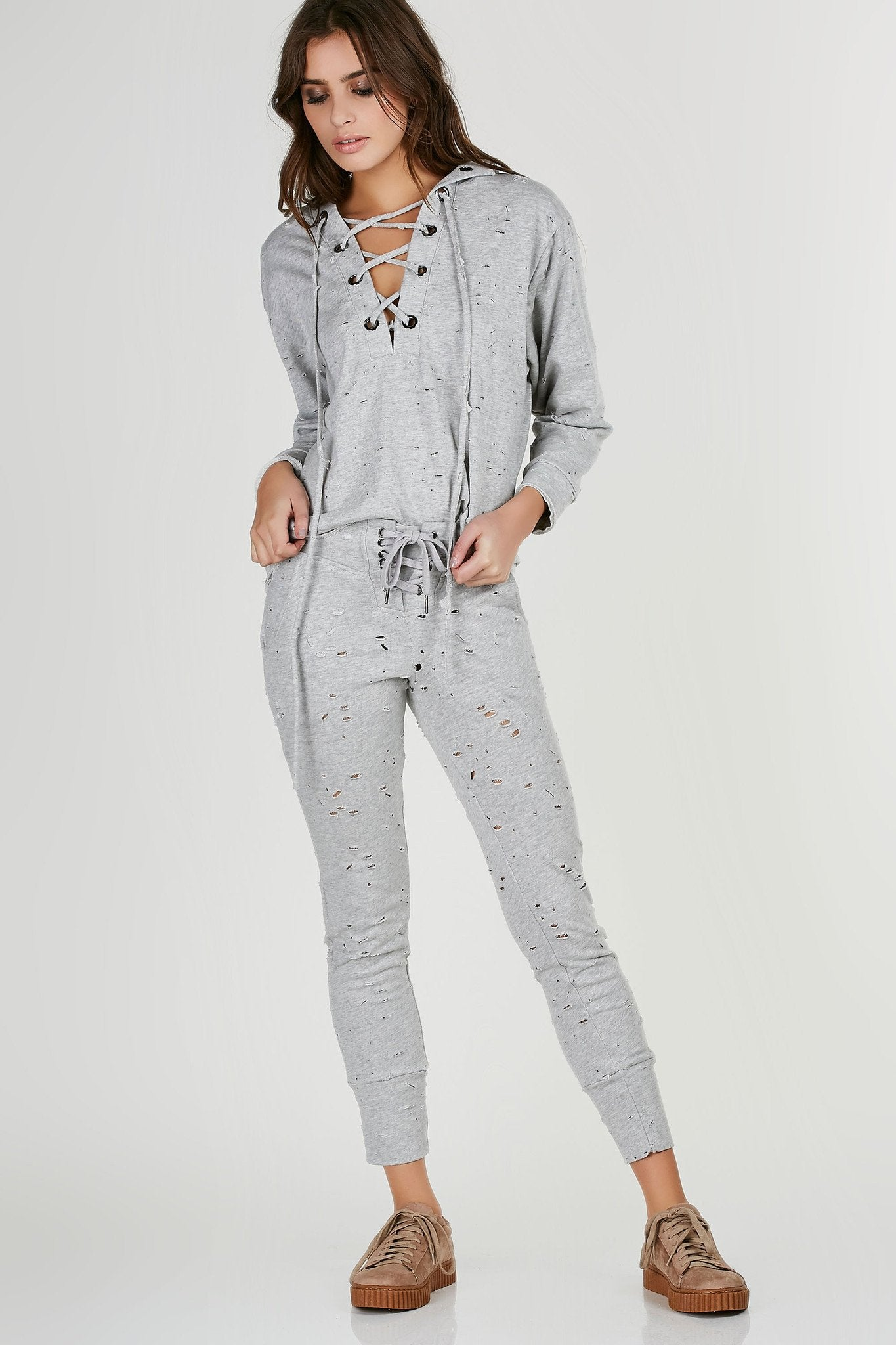Mid rise sweatpants with trendy lace up detailing at waist. Distressed throughout with functional pockets. Comes in a set with matching top sold separately.