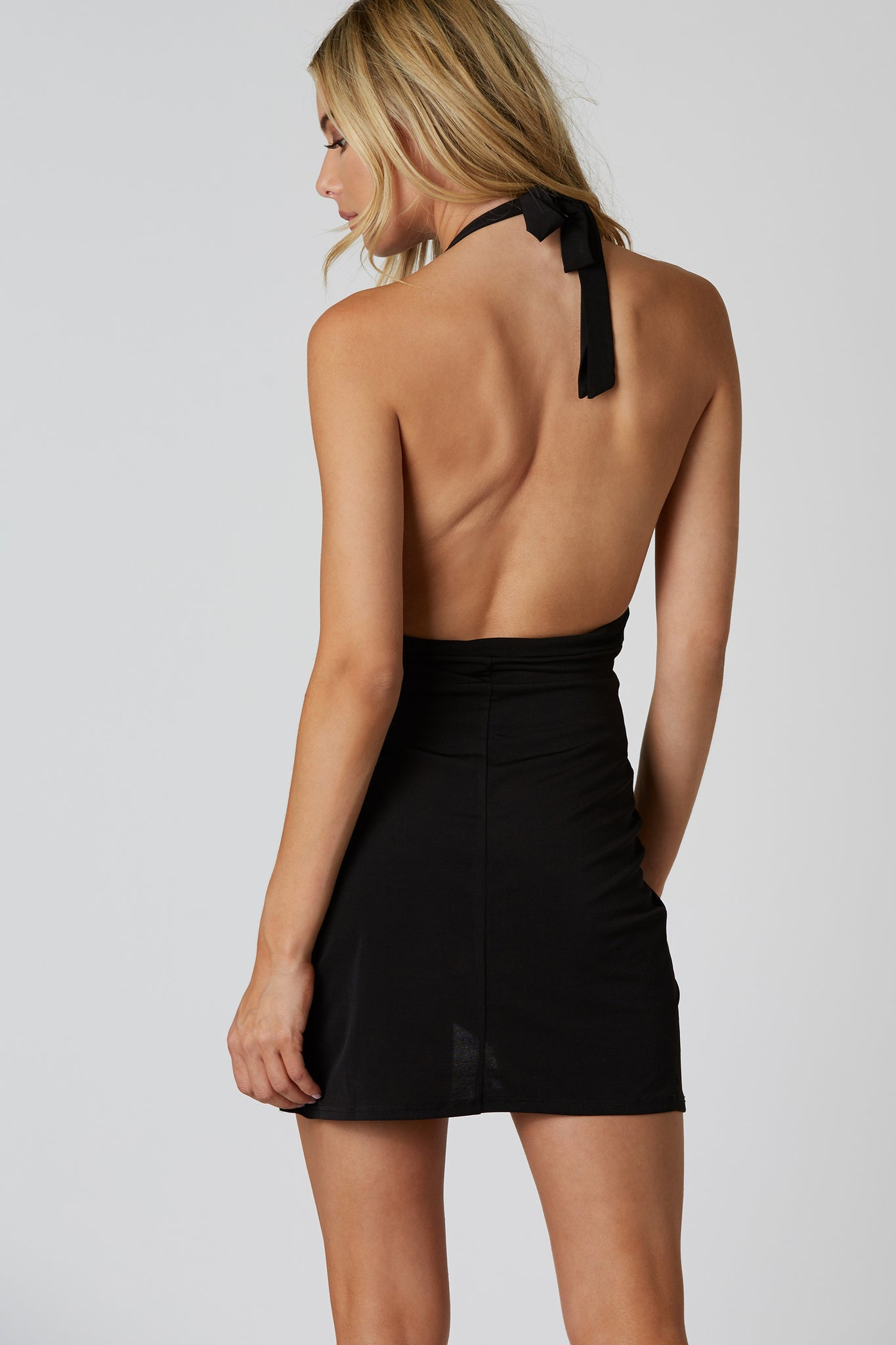 Sleeveless halter mini dress made of smooth slinky material. Classic V-neckline with overlap finish and open back.