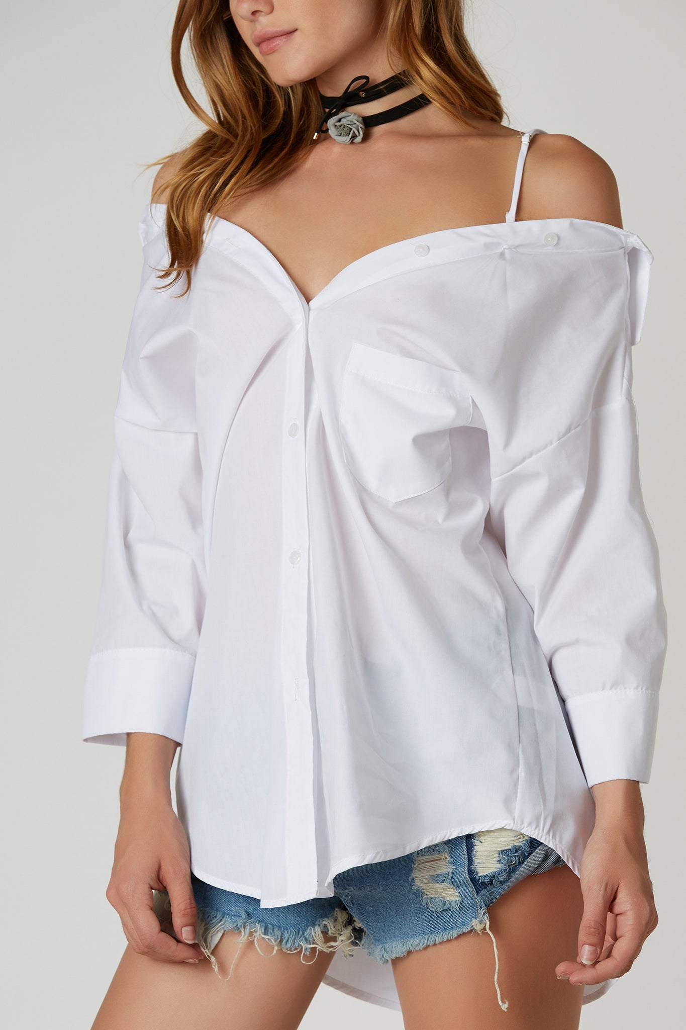 Chic cold shoulder blouse with oversized fit. Button front closure with longline hem.