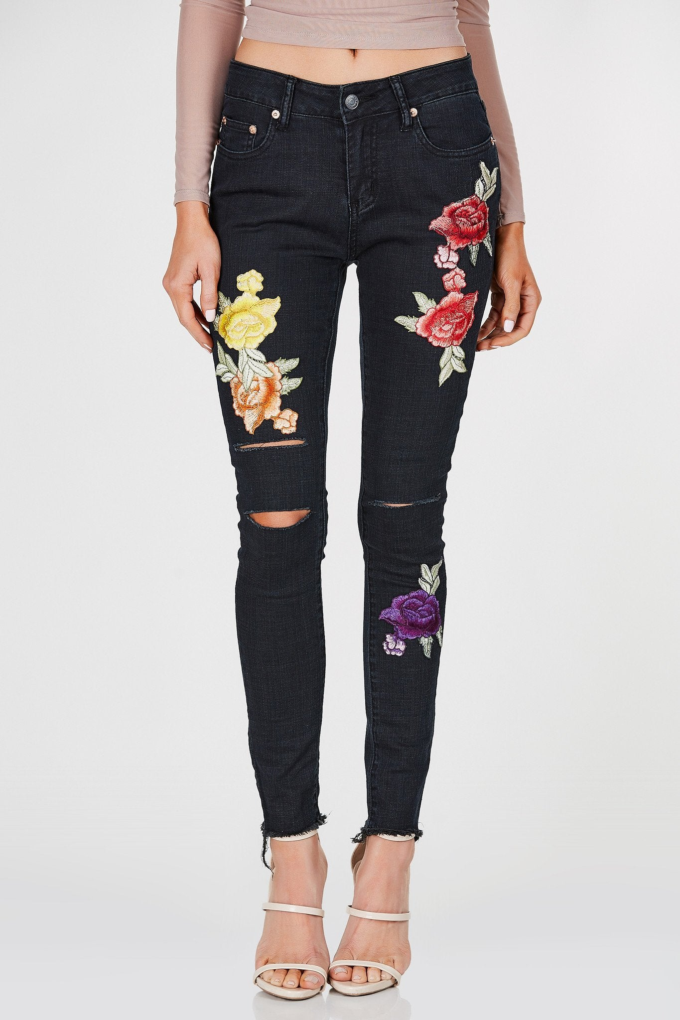 Mid rise dark wash skinnies with flower patches in front. Distressing at knees with raw hem.