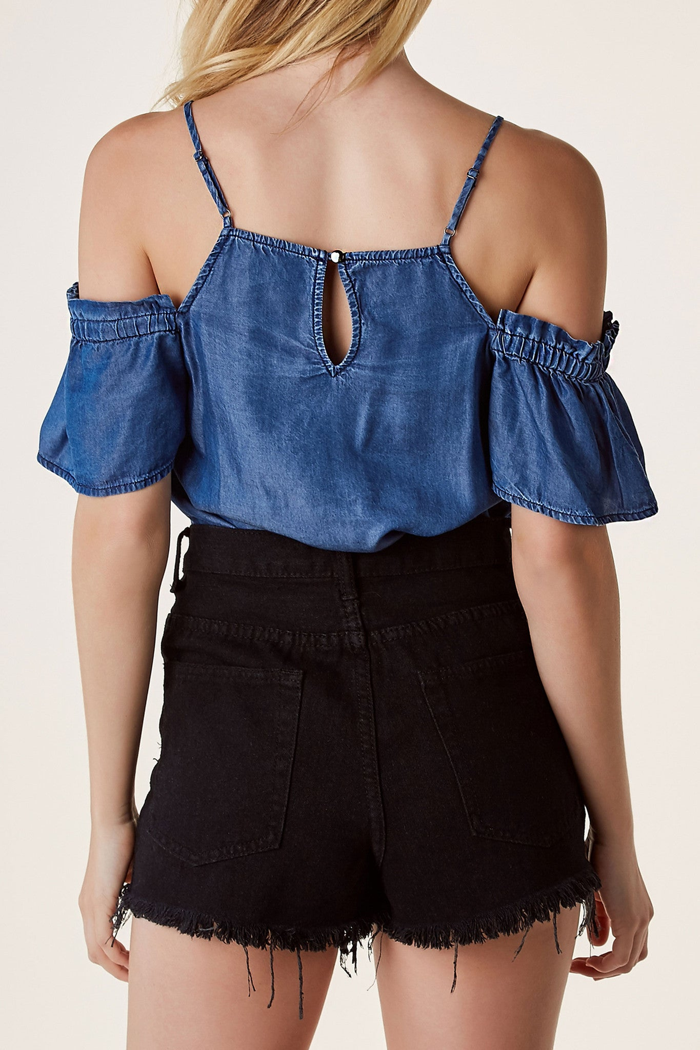 Cold shoulder chambray top with oversized fit. Straight neckline with adjustable shoulder straps and ruffle trim detailing at sleeves.
