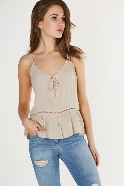 Flowy sleeveless tank top with flirty ruffle style hem. Lace up design with peek-a-boo crochet panel throughout.
