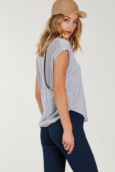 Soft relaxed fit tee with rounded neckline and cap sleeves. Contrast perforated lining in back under racerback finish with rounded hem.