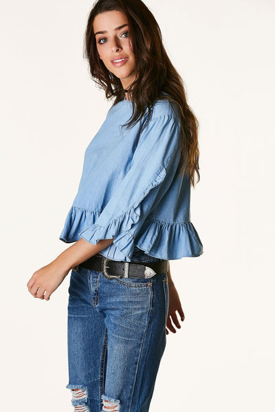 Crew neck chambray top with cropped sleeves and hem. Flirty ruffle trim all around with keyhole cut out and button closure in back.