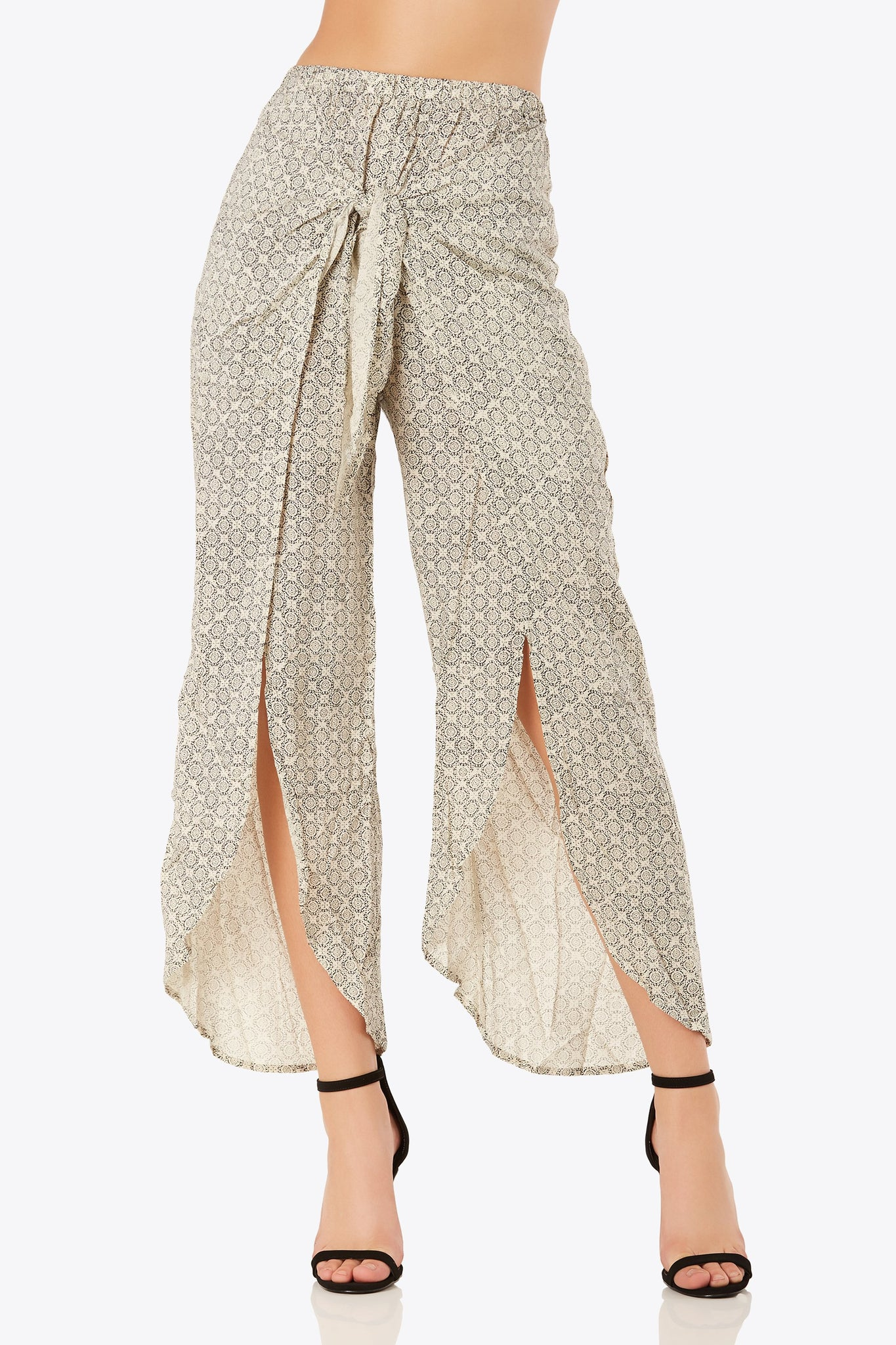 Flowy high rise printed pants with chic front wrap design. Stretchy elasticized waistband with bold front slit detailing.