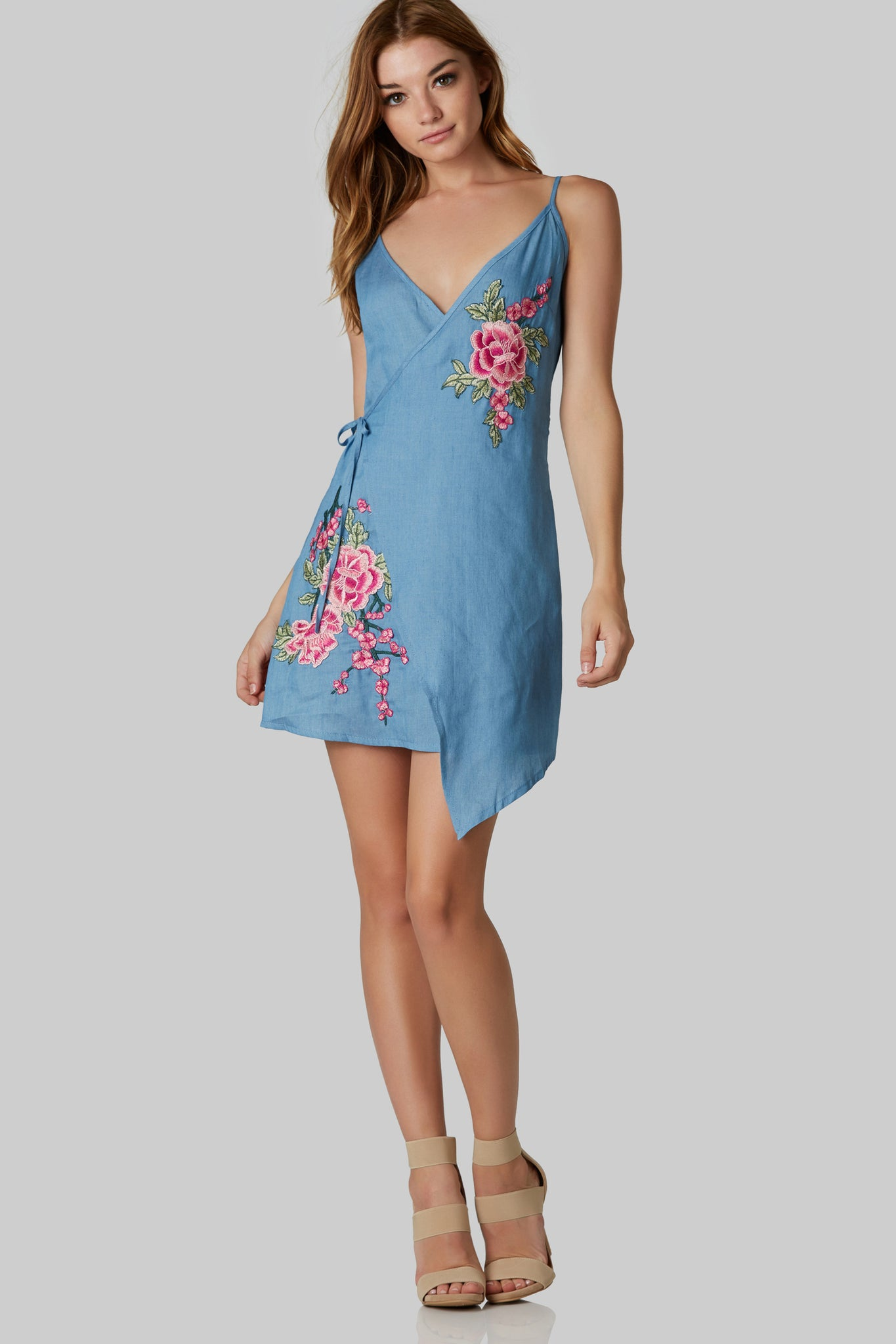 Sleeveless chambray mini dress with front wrap closure. Colorful floral patches and adjuistable should straps.