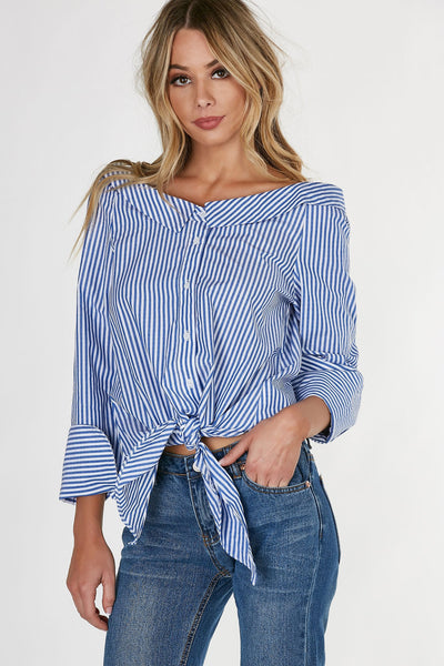 Long sleeve oversized blouse with flattering boat neckline. Button front with tie at hem for added detail.