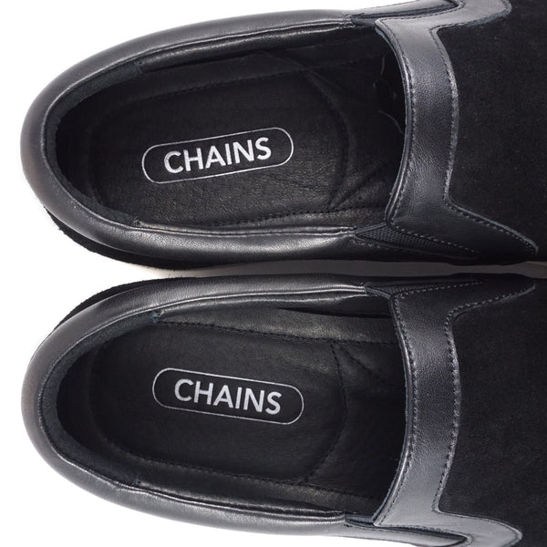 Black cow suede slip-on slide sneaker from CHAINS with signature metal badge on the side