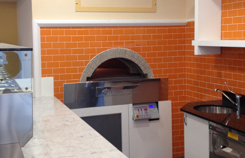 A milano fired oven enclosed by a orange brick wall design.