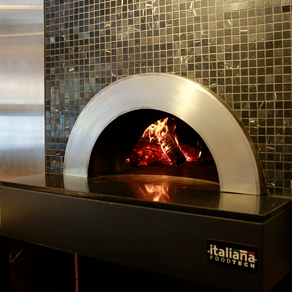 an enclosed Milano fired oven in use, with custom tile pattering around the enclosure.