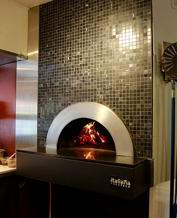 Milano fired oven enclosed within a decorated wall with custom tiling.