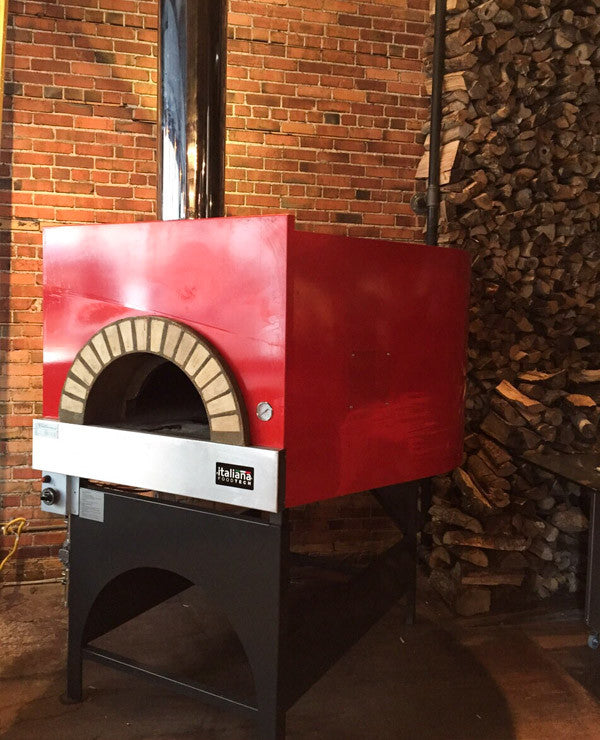Milano fired oven with a red finish, installed and ready for use.