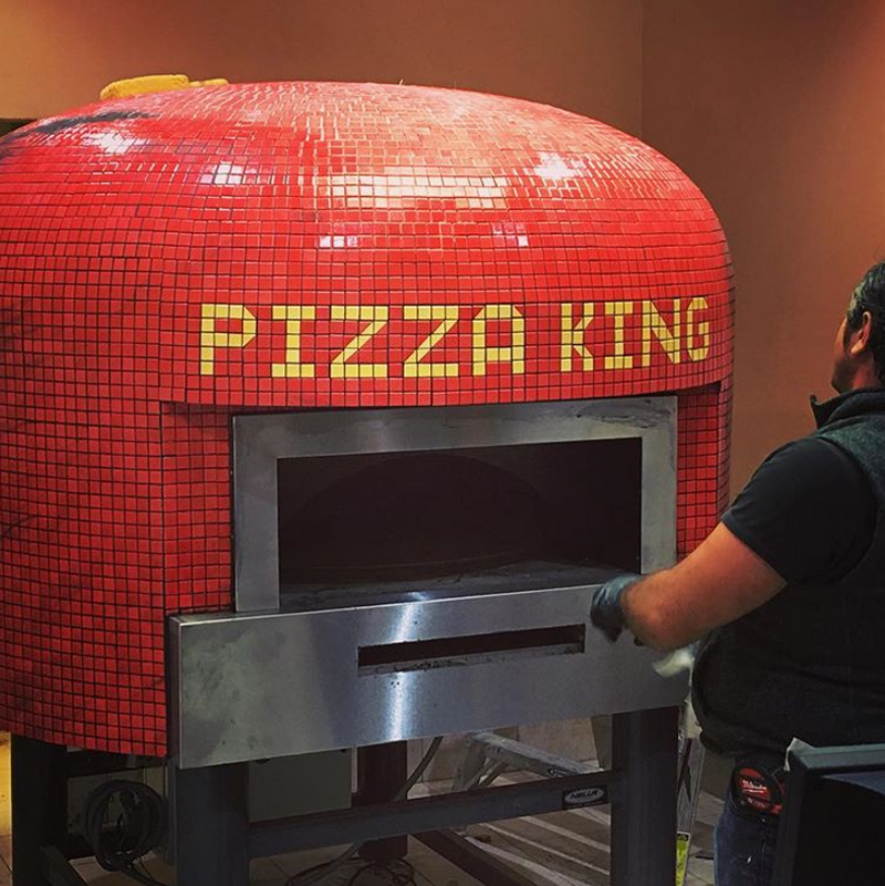 A bright red Napoli fired oven with a custom branded tiling for Pizza King.