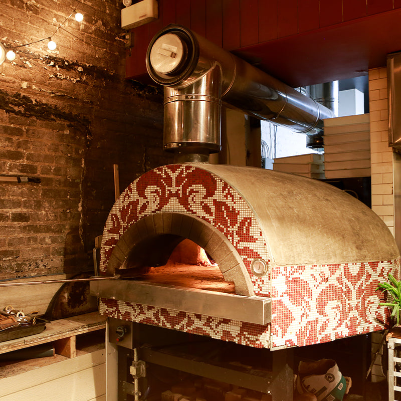 A Roma fired oven with a white and red pattern tile finish.
