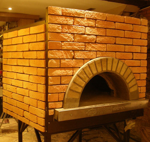 an enclosed Milano fired oven with a custom gold brick tiling design.