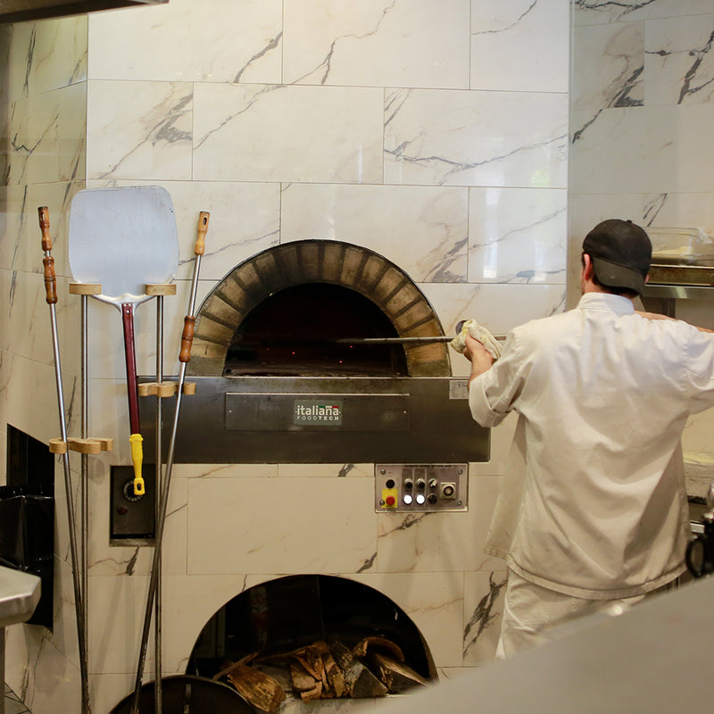 Milano fired oven enclosed within a white marbled wall.