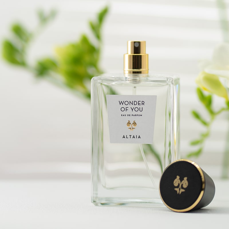 Lifestyle shot of ALTAIA Wonder of You Eau de Parfum (100 ml) with top of bottle off and posed facing front