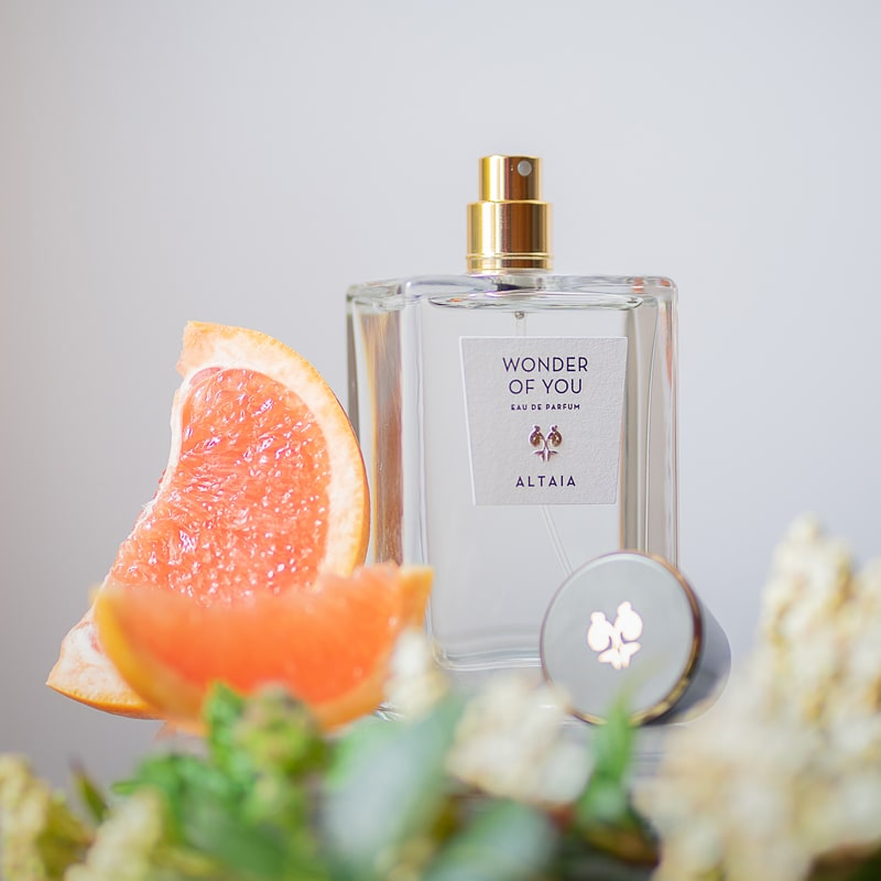 Lifestyle shot of ALTAIA Wonder of You Eau de Parfum (100 ml) with citrus slices and ingredients in the foreground
