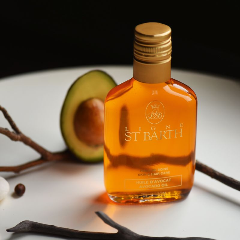 Beauty shot of Ligne St. Barth Avocado Oil 200 ml with half of an avocado and twig in the background