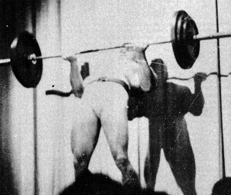 A Young Arnold Schwarzenegger Performing a Cheat Curl