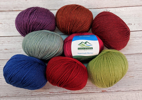 Photo of eight different balls of colorful superwash merino light worsted yarn by Coeur d'Alene Yarns.