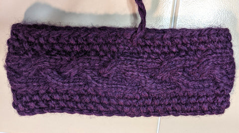 Photo of a purple knit headband with a cable going down the center. Photo shows the nearly invisible seam made with a kitchener stitch join.