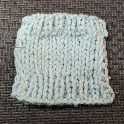 Photo of a knit square in a light blue yarn. The swatch has stockinette in the center and ribbed edging on the top and bottom.