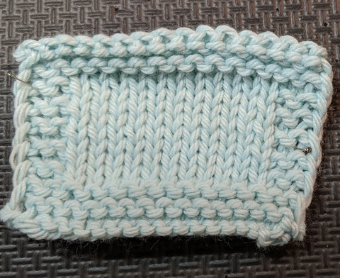 Photo of a knit square in a light blue yarn. Stockinette is in the center of the swatch, with garter stitch around all four edges.