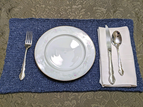 Photo of a table place setting. Brown floral table cloth with a denim blue colored knit placemat with a china plate and utensils.