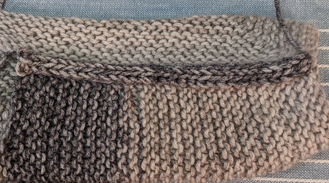 Photo of the left sleeve of the baby surprise jacket in gray where a three stitch applied i-cord was used to seam the shoulder
