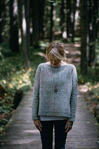 Photo of a woman wearing a light blue knit sweater, the Weekender Sweater by Andrea Mowry