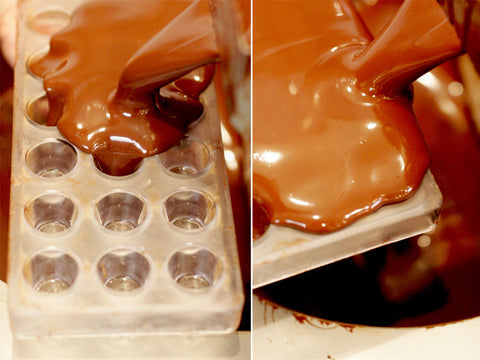 Jest Cafe photo of polycarbonate molds filled with tempered dark chocolate.