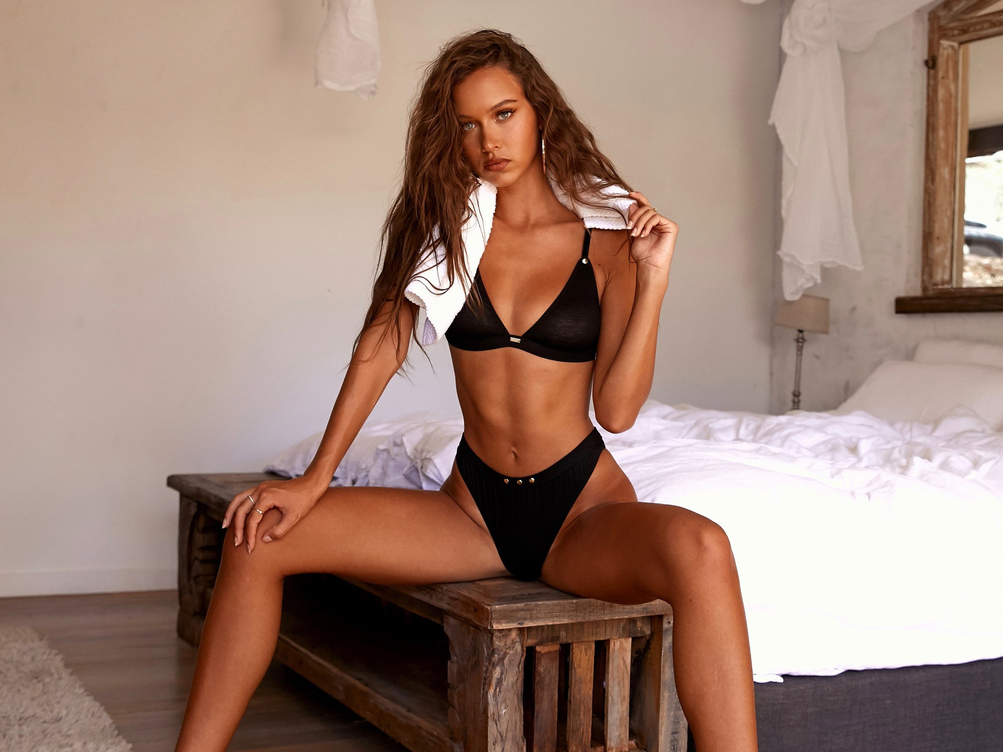 Isabelle Mathers wearing the IAM Black Triangle Bra and Cheeky Brief while sitting down on a bed stool