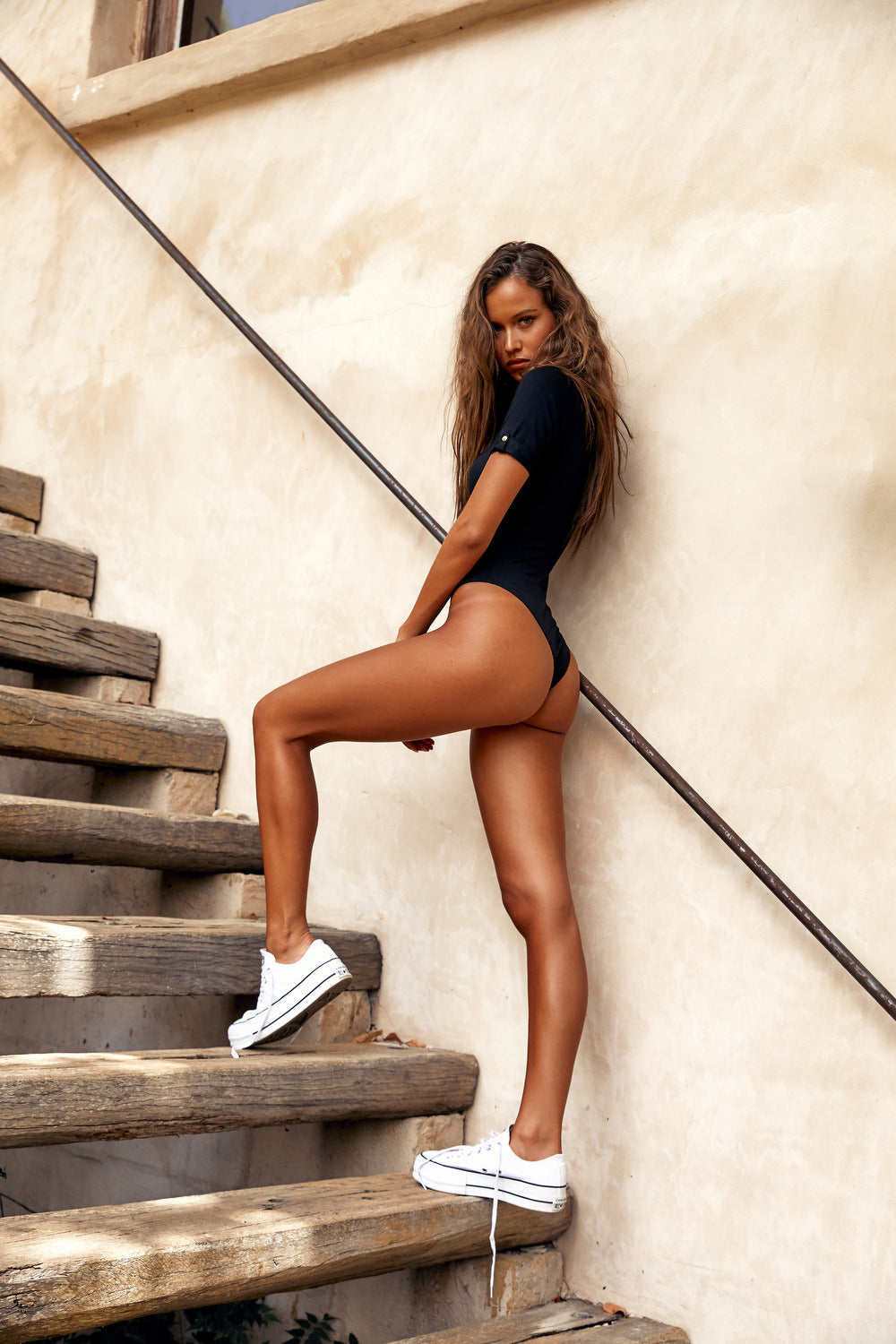 Isabelle Mathers wearing the IAM Black Short Sleeve Bodysuit & white sneakers while going up wooden stairs