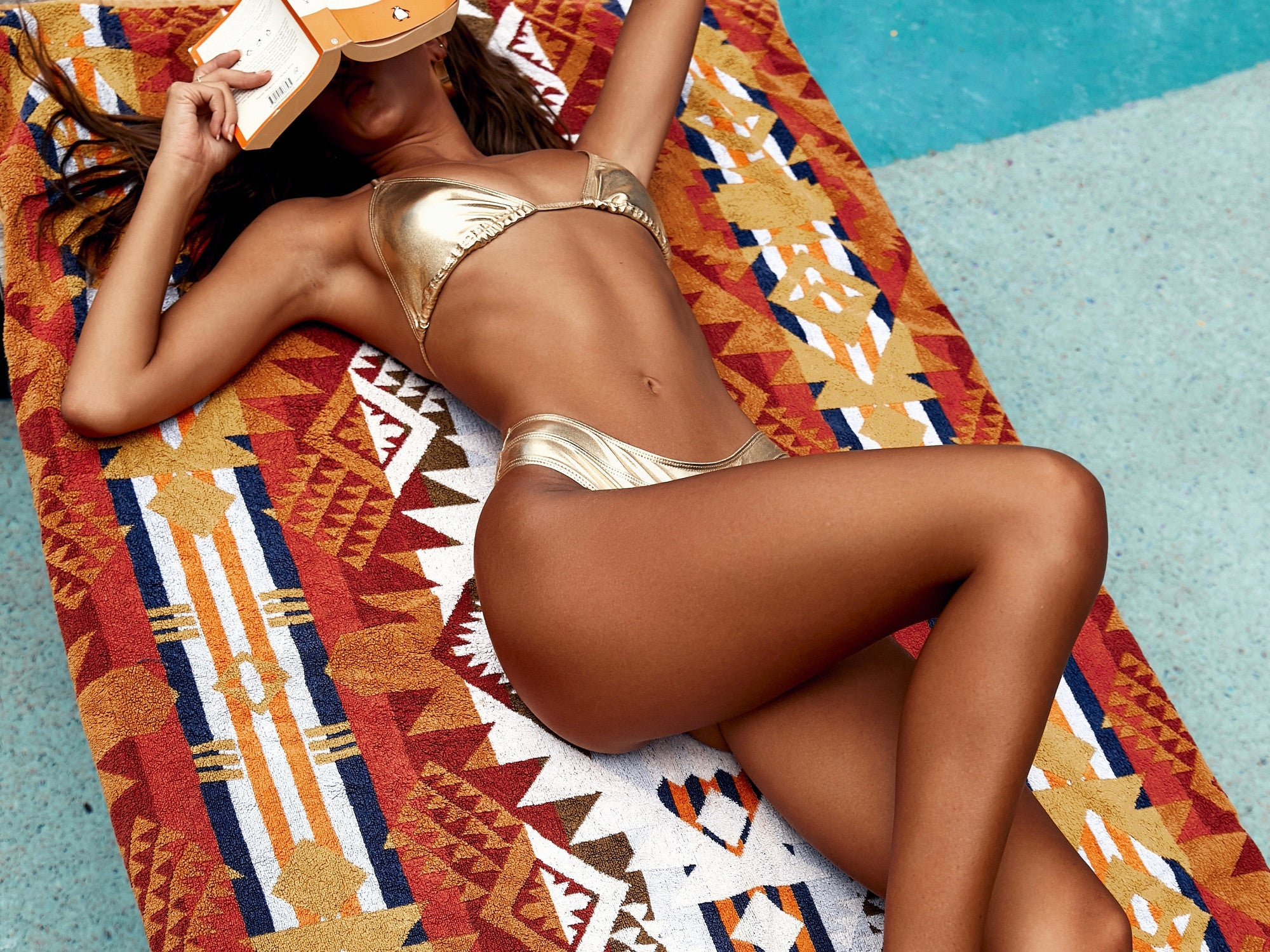Isabelle Mathers wearing the Glam Gold Bikini Set while lying on a pool lounge chair