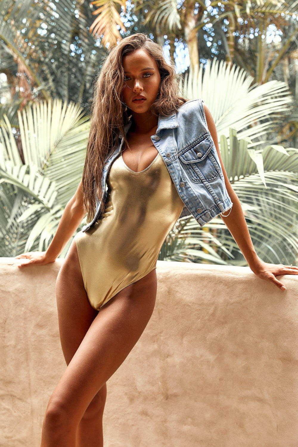 Isabelle Mathers wearing the Glam Gold One Piece Bodysuit under a denim jacket