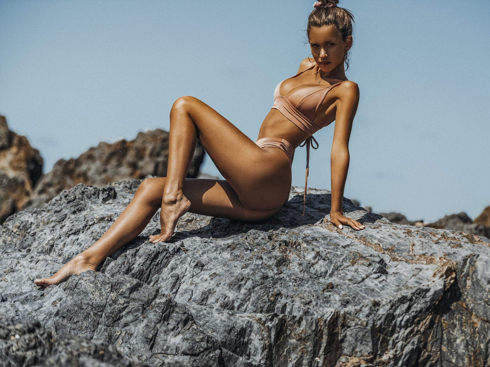 Isabelle Mathers wearing the For You Bikini Triangle Set Rosebud while sitting on a rock on the beach