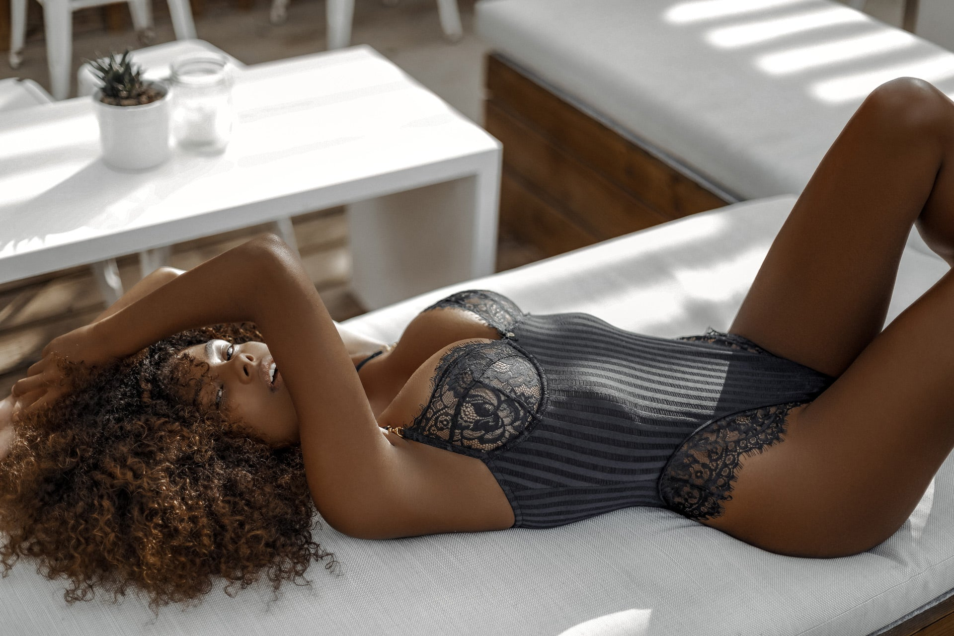 Tina Kunakey reclining in the Bliss Black Bodysuit