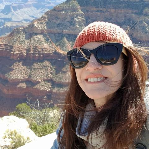 Julia Kerr Shares her  Mental Health story for RUOK Day. Image: Selfie image mental health warrior woman Julia Kerr with brown hair, orange beanie and sunglasses smiling. The grand canyon is behind her.