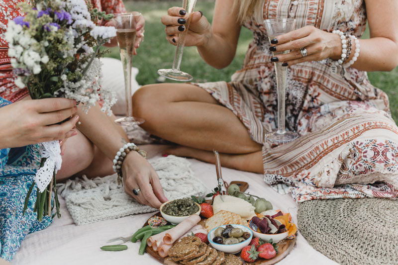 Three friends sharing a platter.  They are wearing autumn fall colors and white howlite and jasper crystal bracelets for healing and spirituality