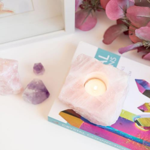 Candle Crystal Homewares Love  Rose Quartz Rough Cut. Pale Pink Square cut rose quartz crystal for tealight candle.  Crystal Homewares.   Candle sits on top of colourful book with amethyst crystal and flowers in background