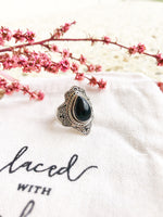 Side view of tear shaped onyx crysta set in stirling silver ring.   Cherry blossom is behind the ring. Embroidered laced with kindness is at the foreground