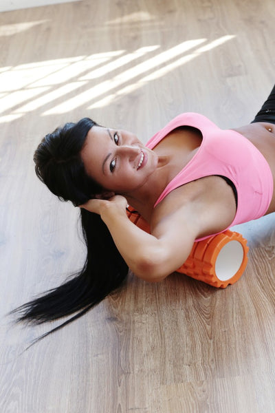 Girl in the gym foam rolling thorasic