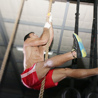 Man using climbing rope at a CrossFit gym