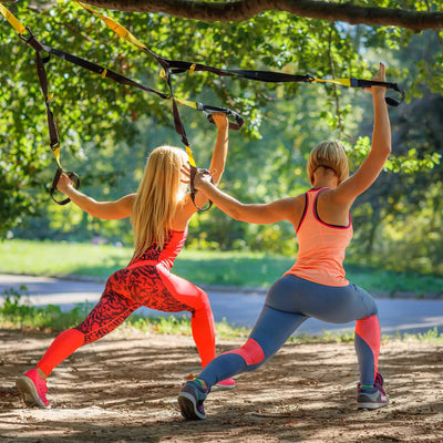 Suspension trainer two women exercising in park