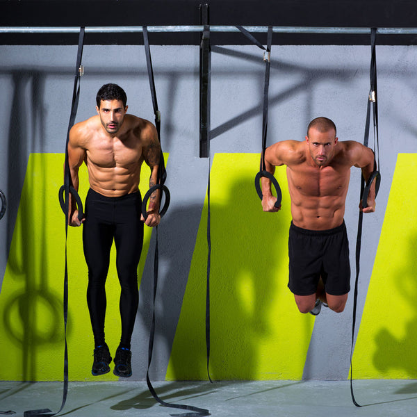 Two men on gymnastic rings in a gym doing tricep dips